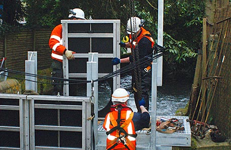 Installing a penstock sluice structure in a flooded river