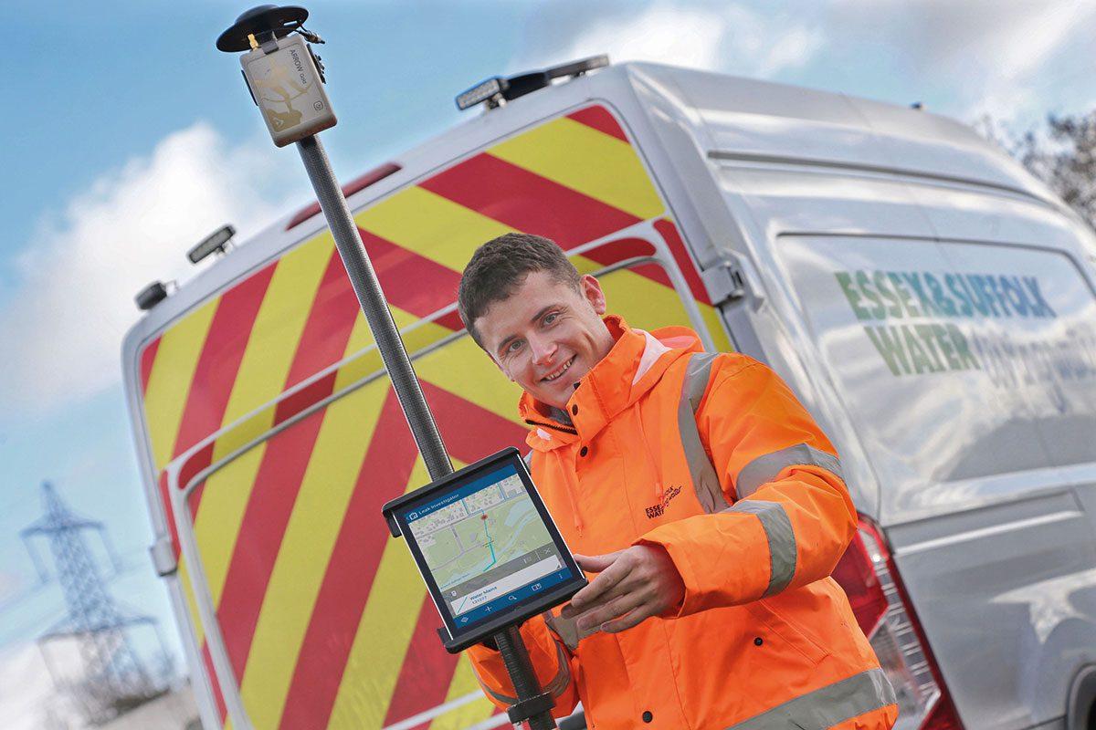 man holding tablet infront van