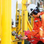 worker checking gas valve